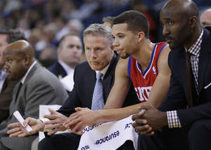 Photo - Philadelphia 76ers head coach Brett Brown, left, talks to point guard Michael Carter-Williams, center, in the closing minutes of a 123-80 loss to the Golden State Warriors during the second half of an NBA basketball game on Monday, Feb. 10, 2014, in Oakland, Calif. (AP Photo/Marcio Jose Sanchez)