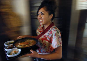 Photo - In this April 4, 2014 photo, food server Kathy Nguyen delivers a traditional Japanese meal to a customer at Domo, in Denver. Owner and head chef Gaku Homma has shaped Domo into a place where you can immerse yourself in Japanese culture, by visiting a museum that evokes a northern Japanese farmhouse, strolling in a garden studded with Buddha statues, or even taking a martial arts class in the converted former warehouse where the restaurant compound is located. Homma uses the profits not to enrich himself financially, but instead funds orphanages around thew world. (AP Photo/Brennan Linsley)