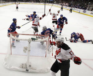 Photo -   New Jersey Devils' Ilya Kovalchuk, bottom right, of Russia, reacts after scoring a goal against the New York Rangers in the first period of Game 2 of an NHL hockey Stanley Cup Eastern Conference final playoff series, Wednesday, May 16, 2012, at New York's Madison Square Garden. The Devils won 3-2. (AP Photo/Julio Cortez)