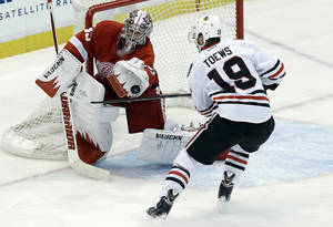 Photo - Detroit Red Wings goalie Jimmy Howard stops a Chicago Blackhawks center Jonathan Toews (19) shot during the second period in Game 4 of the Western Conference semifinals in the NHL hockey Stanley Cup playoffs in Detroit, Thursday, May 23, 2013. (AP Photo/Paul Sancya)