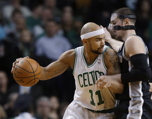 Photo - Boston Celtics guard Jerryd Bayless (11) attempts to drive around San Antonio Spurs point guard Nando de Colo during the first half of an NBA basketball game in Boston, Wednesday, Feb. 12, 2014. (AP Photo/Stephan Savoia)