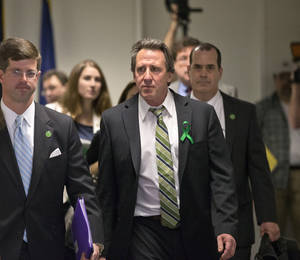 Photo - Neil Heslin, center, whose 6-year-old son Jesse was killed in the mass shooting in Newtown, Conn., arrives with other victims' families to meet privately on Capitol Hill in Washington, Tuesday, April 9, 2013, with Sen. Richard Blumenthal, D-Conn., and Sen. Chris Murphy, D-Conn. Heslin gave moving testimony during a Senate Judiciary Committee hearing in February on the proposed assault weapons ban.  (AP Photo/J. Scott Applewhite)
