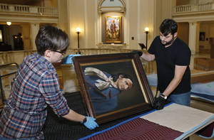 "Photo - Kristi Wyatt, left,  and Brad Stevens, of the Fred Jones Jr. Museum of Art at the University of Oklahoma, prepare artwork for shipping to Oklahoma State University's museum of art, at the state Capitol in Oklahoma City, Tuesday, June 10, 2014. The painting they are packing is titled ""Chief Peter Pitchlynn"". Museum officials from the state's two flagship universities are packing 55 separate pieces of art from the Oklahoma Senate collection to ship to Stillwater for display in a new university museum. (AP Photo/Sue Ogrocki)"