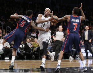Photo - Detroit Pistons guard Kentavious Caldwell-Pope (5) fouls Brooklyn Nets forward Paul Pierce (34) as Detroit Pistons guard Brandon Jennings (7) defends in the first half of an NBA basketball game, Sunday, Nov. 24, 2013, in New York. (AP Photo/Kathy Willens)