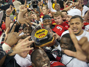 photo - Texas Tech players celebrate with the championship trophy after winning the Meineke Car Care Bowl NCAA college football game against Minnesota, Friday, Dec. 28, 2012, in Houston. Texas Tech defeated Minnesota 34-31. (AP Photo/Dave Einsel)