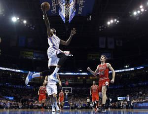 Photo - Oklahoma City Thunder forward Kevin Durant (35) shoots in front of Chicago Bulls forward Mike Dunleavy (34) during the first quarter of an NBA basketball game in Oklahoma City, Thursday, Dec. 19, 2013. (AP Photo/Sue Ogrocki)
