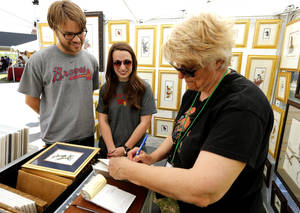 Photo -  Ben and Abby Cook, Norman, purchase art by Carolyn Mejstrik at the annual Mayfair Festival of the Arts in Norman. PHOTO BY STEVE SISNEY, THE OKLAHOMAN  <strong>STEVE SISNEY -   </strong>