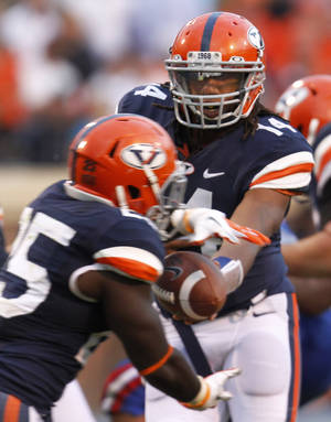 photo -   Virginia quarterback Phillip Sims (14) hands the ball off to running back Kevin Parks (25) during the second half of an NCAA college football game at Scott stadium in Charlottesville, Va., Saturday, Sept. 29, 2012. Sims replaced starter Michael Rocco who threw three interceptions. Louisiana Tech won the game 44-38. (AP Photo/Steve Helber)