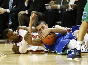 Photo - Oklahma guard Buddy Hield, left, and Texas A&M Corpus Christie guard Cole Martinez, right, fight for the ball in the second half of an NCAA college basketball game in Norman, Okla., Thursday, Dec. 5, 2013. Oklahoma won 78-56. (AP Photo/Sue Ogrocki)