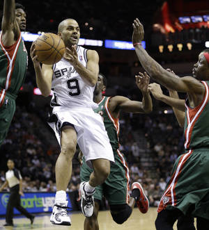 Photo - San Antonio Spurs' Tony Parker (9), of France, drives between Milwaukee Bucks' Larry Sanders,left, and Marquis Daniels, right, during the first quarter of an NBA basketball game on Wednesday, Dec. 5, 2012, in San Antonio. San Antonio won 99-95. (AP Photo/Eric Gay)