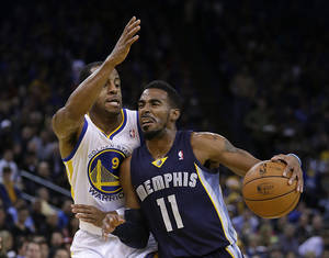 Photo - Memphis Grizzlies' Mike Conley (11) drives the ball against Golden State Warriors' Andre Iguodala (9) during the first half of an NBA basketball game on Wednesday, Nov. 20, 2013, in Oakland, Calif. (AP Photo/Ben Margot)