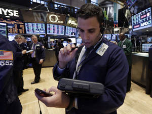 Photo - Trader Craig Spector works on the floor of the New York Stock Exchange Wednesday, March 19, 2014. Stocks are slightly lower in early trading on Wall Street as traders wait for the latest policy decision from the Federal Reserve. (AP Photo/Richard Drew)