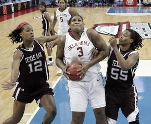 Photo - Courtney Paris shoots guarded by LaToya Micheaux and Danielle Gant (55) during the first half of the game between the University of Oklahoma and Texas A&M Aggies Saturday afternoon. Photo by Steve Sisney.