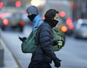 Photo - Commuters bundle up against extreme cold conditions Tuesday, Jan. 22, 2013, in Chicago. Temperatures in the area were hovering around zero with sub-zero wind chill reading hitting 10 below. Forecasters say waves of frigid Arctic air began moving over the region Saturday night Jan. 19, 2013. (AP Photo/M. Spencer Green)