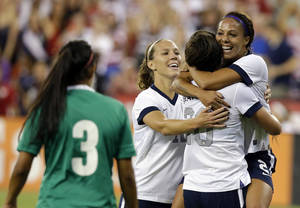 Photo - Mexico's defender Bianca Sierra (3) watches as United States midfielder Lauren Holiday (12),  forward Abby Wambach (20) and forward Sydney Leroux (2) celebrate Leroux's first goal in the first half of an international friendly soccer match at RFK Stadium Tuesday, Sept. 3, 2013, in Washington. (AP Photo/Alex Brandon)