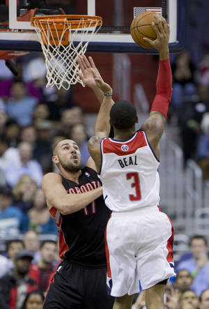 Photo - Toronto Raptors Jonas Valanciunas (17) of Lithuania defends as Washington Wizards Bradley Beal (3) shoots the ball and scores during the first half of an NBA basketball game in Washington, Tuesday, Feb. 18, 2014. (AP Photo/Manuel Balce Ceneta)