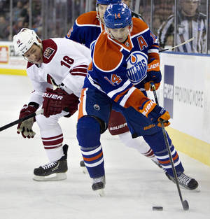 photo - Phoenix Coyotes' David Moss (18) chases Edmonton Oilers' Jordan Eberle (14) during the first period of an NHL hockey game in Edmonton, Alberta, on Saturday, Feb. 23, 2013. (AP Photo/The Canadian Press, Jason Franson)