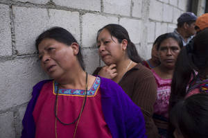 Photo - Relatives of victims react as police take away the bodies, not seen, after an attack in San Jose Nacahuil, on the outskirts of Guatemala City, Sunday, Sept. 8, 2013. Men firing from a car poured gunshots into three cantinas in this rural town, killing at least 10 people and injuring 19, local firefighters said Sunday. (AP Photo/Moises Castillo)