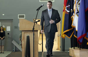 Photo - With his wife Amy, left, watching Ryan Pitts walks on the stage to talk with reporters Thursday June 26, 2014 in Concord, N.H. Pitts will wear the nation's highest award, the  Medal of Honor  for combat valor after he continued to fight after being wounded in one of Afghanistan's bloodiest battles. He insisted that the medal belongs to all of his comrades who fought and died that day. Pitts will receive the medal next month at the White House.(AP Photo/Jim Cole)