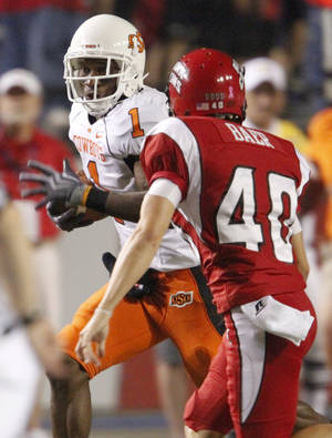 Photo - OSU's Joseph Randle tries to get past Louisiana-Lafayette's Brett Baer during the football game between the University of Louisiana-Lafayette and Oklahoma State University at Cajun Field in Lafayette, La., Friday, October 8, 2010. Photo by Bryan Terry, The Oklahoman