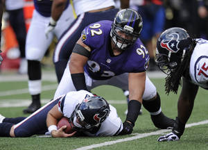 Photo - Baltimore Ravens defensive tackle Haloti Ngata (92) lifts himself off of Houston Texans quarterback Matt Schaub after sacking him in the first half of an NFL football game Sunday, Sept. 22, 2013, in Baltimore. (AP Photo/Nick Wass)