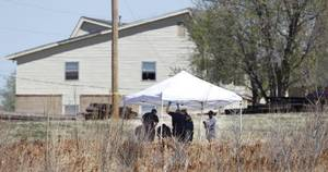 Photo - Investigators work on a crime scene in the death of Rosalin Reynolds, 8, on Wednesday in a field behind the Watonga apartment complex where she lived. <strong>Steve Gooch - The Oklahoman</strong>