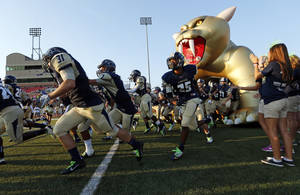 Photo - The Southmoore Sabercats take the field before a high school football game between Southmoore and Carl Albert at Moore Schools Stadium in Moore, Okla., Thursday, Sept. 5, 2013.  Photo by Nate Billings, The Oklahoman