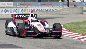 Photo - Driver Helio Castroneves takes the second turn during a practice session for the IndyCar Detroit Grand Prix auto race on Belle Isle in Detroit, Friday, May 30, 2014. (AP Photo/Bob Brodbeck)