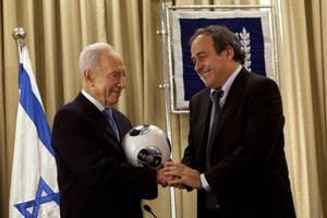 Photo - Israel's President Shimon Peres, left, shakes hands with UEFA President Michel Platini during a meeting at the President's residence in Jerusalem,  Thursday, Nov. 29, 2012.  Israel will host the under-21 Championship in June 2013. (AP Photo/Sebastian Scheiner)