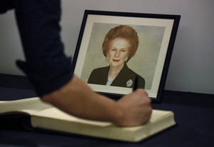 Photo - A man signs the condolence book in front of a  picture of former British Prime Minister Margaret Thatcher at the British Consulate in Hong Kong Tuesday, April. 9, 2013. Her spokesman said Thatcher died Monday morning of a stroke. (AP Photo/Vincent Yu)