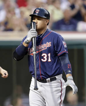 Photo - Minnesota Twins' Oswaldo Arcia kisses his bat after striking out against Cleveland Indians starting pitcher Scott Kazmir in the seventh inning of a baseball game, Friday, June 21, 2013, in Cleveland. (AP Photo/Tony Dejak)