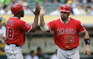 Photo -   Los Angeles Angels' Torii Hunter, left, and Albert Pujols (5) celebrate after scoring against the Oakland Athletics in the third inning of a baseball game, Wednesday, Sept. 5, 2012, in Oakland, Calif. Both scored on a single by Howie Kendrick. (AP Photo/Ben Margot)