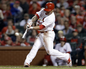 Photo - St. Louis Cardinals' Kolten Wong hits a two-run triple during the second inning of a baseball game against the Cincinnati Reds on Tuesday, April 8, 2014, in St. Louis. (AP Photo/Jeff Roberson)