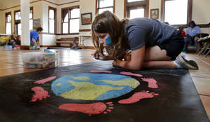 Photo - Alex Morgan, 11, blows dust off her work Saturday at a children's chalk art contest at Santa Fe Depot in Norman. The contest was to raise awareness for the CROP Walk to Stop Hunger. PHOTOs BY STEVE SISNEY, THE OKLAHOMAN