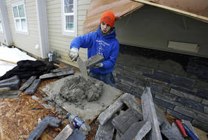 Photo - In this Jan. 10, 2014, photo, Trevor Davis puts concrete on stone for the foundation of a new home, in Pepper Pike, Ohio. The National Association of Home Builders reports on sentiment among U.S. builders on Tuesday, Feb. 18. (AP Photo/Tony Dejak)