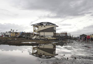 Photo - Survivors walk past damaged houses at typhoon ravaged Tacloban city, Leyte province, central Philippines on Tuesday, Nov. 12, 2013. The Philippines emerged as a rising economic star in Asia but the trail of death and destruction left by Typhoon Haiyan has highlighted a key weakness: fragile infrastructure resulting from decades of neglect and corruption. (AP Photo/Aaron Favila)