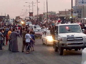 Photo - In this still image posted on a militant Twitter account on Wednesday, June 11, 2014, which has been authenticated based on its contents and other AP reporting, militants parade down a main road in Mosul, Iraq.  Iraqi officials say al-Qaida-inspired militants who this week seized much of the country's Sunni heartland have pushed into an ethnically mixed province northeast of Baghdad, capturing two towns there.(AP Photo/militant source via Twitter)