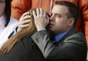 photo - Mourners embrace following funeral services for Connecticut elementary shooting victim Emilie Parker, Saturday, Dec. 22, 2012, at The Church of Jesus Christ of Latter-day Saints, in Ogden, Utah. (AP Photo/Rick Bowmer)