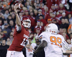 Photo -   Oklahoma quarterback Landry Jones (12) passes for a 2-point conversion under pressure from Oklahoma State defensive tackle Calvin Barnett (99) in the fourth quarter of an NCAA college football game in Norman, Okla., Saturday, Nov. 24, 2012. Oklahoma won in overtime, 51-48. (AP Photo/Sue Ogrocki)