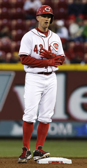 Photo - Cincinnati Reds starting pitcher Mike Leake adjusts his gloves while standing on second base after hitting a double off Pittsburgh Pirates starting pitcher Gerrit Cole in the third inning of a baseball game, Tuesday, April 15, 2014, in Cincinnati. (AP Photo/Al Behrman)