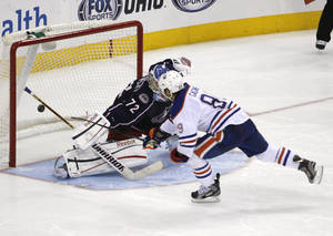 Photo - The stick of Columbus Blue Jackets goalie Sergei Bobrovsky (72) stops a shot by Edmonton Oilers' Sam Gagner (89) during the shootout in their NHL hockey game, Tuesday, March, 5, 2013, in Columbus, Ohio. (AP Photo/Mike Munden)