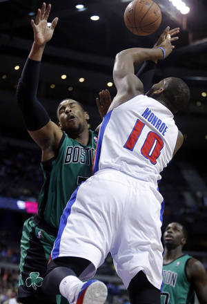 Photo - Detroit Pistons center Greg Monroe (10) is fouled by Boston Celtics forward Jared Sullinger while taking a shot during the first half of an NBA basketball game Saturday, April 5, 2014, in Auburn Hills, Mich. (AP Photo/Duane Burleson)