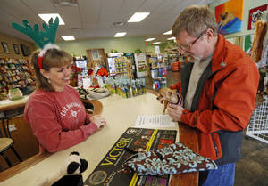Photo - Doyle Tilson and Squeaky, his Chihuahua, visit with owner Trisha Clark at A1 Pet Emporium in Oklahoma City.  Photos by Nate Billings, The Oklahoman