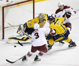 Photo - Nashville Predators goalie Pekka Rinne (35), of Finland, blocks a shot by Phoenix Coyotes defenseman Keith Yandle (3) in the third period of an NHL hockey game on Thursday, April 10, 2014, in Nashville, Tenn. Predators' Shea Weber (6). Phoenix Coyotes right wing Shane Doan (19)  also defend. The Predators won 2-0. (AP Photo/Mark Humphrey)