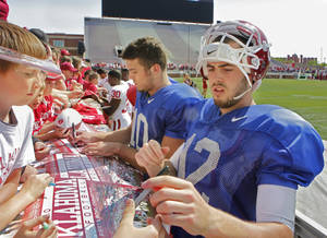 Photo - Quarterbacks Blake Bell (10) and Landry Jones (12) sign autographs after the University of Oklahoma Sooner's (OU) Spring Football game at Gaylord Family-Oklahoma Memorial Stadium on Saturday, April 16, 2011, in Norman, Okla.  