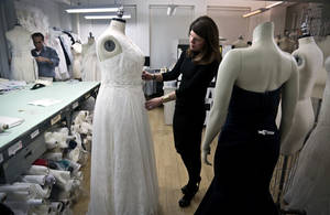 Photo - In this Dec. 17, 2013 photo, David's Bridal senior vice president Michele von Plato, right, arranges a dress on a plus-size mannequin in New York.  David's Bridal, the nation's largest bridal chain, started changing its fit mannequins used to create  gowns to reflect the average body.  (AP Photo/Bebeto Matthews)