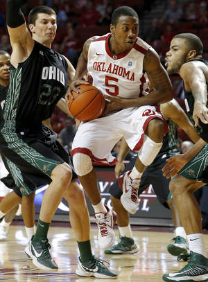 Photo - Oklahoma's Je'lon Hornbeak (5) goes between Ohio's Ivo Baltic (23) and Reggie Keely (30) during an NCAA college basketball game between the University of Oklahoma (OU) and Ohio at the Lloyd Noble Center in Norman, Saturday, Dec. 29, 2012. Oklahoma won 74-63. Photo by Bryan Terry, The Oklahoman