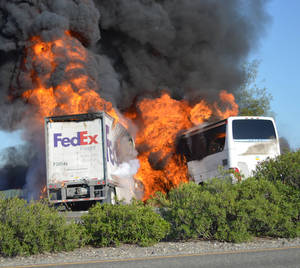 Photo - Massive flames engulf a tractor-trailer and a tour bus just after they collide on Interstate 5, Thursday, April, 10, 2014, near Orland, Calif. At least 10 people were killed in the crash, authorities said. (AP Photo/Jeremy Lockett)
