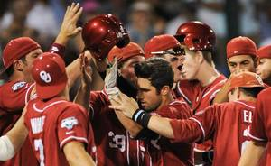 photo - University of Oklahoma's Tyler Ogle, center, is greeted at the dugout after hitting a go-ahead home run against South Carolina in the 12th inning of an NCAA College World Series baseball elimination game, in Omaha, Neb., Thursday, June 24, 2010. (AP Photo/Dave Weaver)