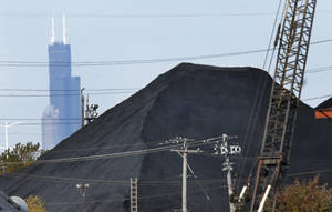 Photo - FILE - In this Oct. 25, 2013 file photo, the Willis Tower in downtown Chicago provides a backdrop to a huge mound of petroleum coke, or petcoke, in the a residential area in the city. Chicago Mayor Rahm Emanuel and Illinois Attorney General Lisa Madigan announced a deal Thursday, Dec. 19, 2013, with an Indiana company that will require it to remove huge black piles of petroleum coke from the city's Southeast Side and accept no other shipments. The material is a powdery byproduct of oil refining that's been accumulating along Midwest shipping channels and sparking health and environmental concerns. (AP Photo/Charles Rex Arbogast, File)